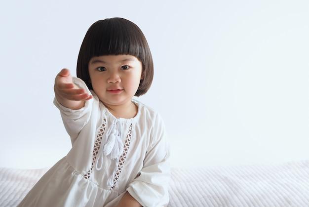 白い壁とベッドの上に座って幸せなアジアの子