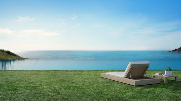 Бассейн с видом на море рядом с террасой и кроватью в современном роскошном домике на пляже с голубым небом