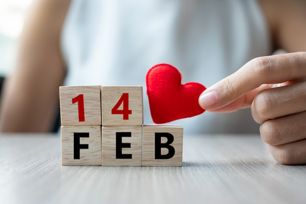 Держит красное украшение в форме сердца с деревянным кубиком