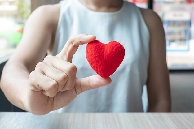 赤いハートを持つ女性の手