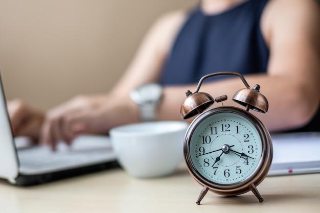 ラップトップを使用して若い実業家と目覚まし時計を閉じる