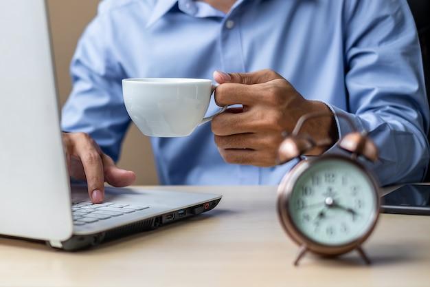 ビジネスマンのラップトップ分析マーケティング計画を使用してコーヒーを飲む