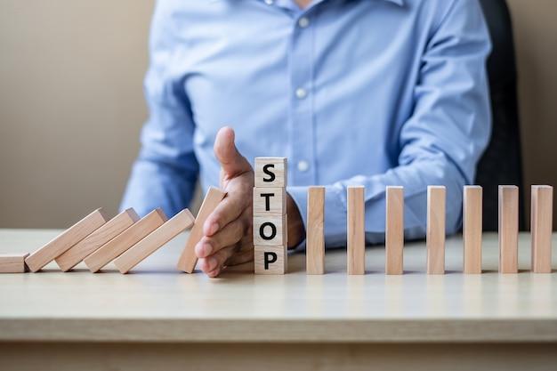 Рука бизнесмена останавливая падающие деревянные блоки или домино