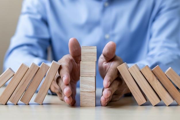 実業家の手が立ち下がりの木製のブロックやドミノを停止