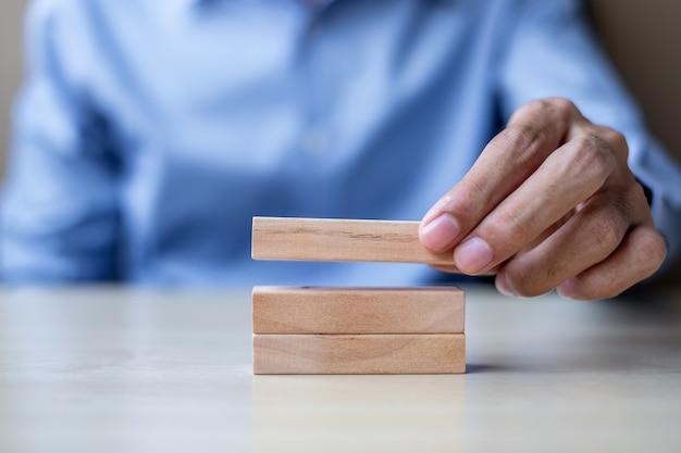 Рука бизнесмена держа деревянные строительные блоки на таблице