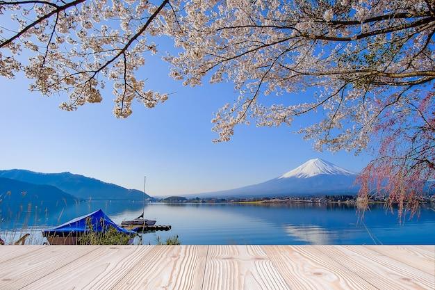 富士山と春の美しいピンクの桜の花の背景の空の木のテーブル