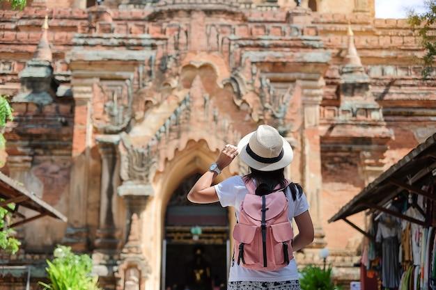 Молодая женщина, путешествующая рюкзаком со шляпой, азиатский путешественник, смотрящий красивые древние храмы и пагоду, ориентир и популярный для туристических достопримечательностей в багане, мьянма. азия трэвел концепция