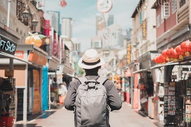Сольный путешественник гуляя на уличный рынок чайна-тауна в сингапуре.