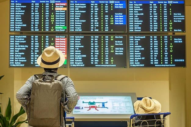 飛行時間をチェックする帽子を持つ若い男旅行者