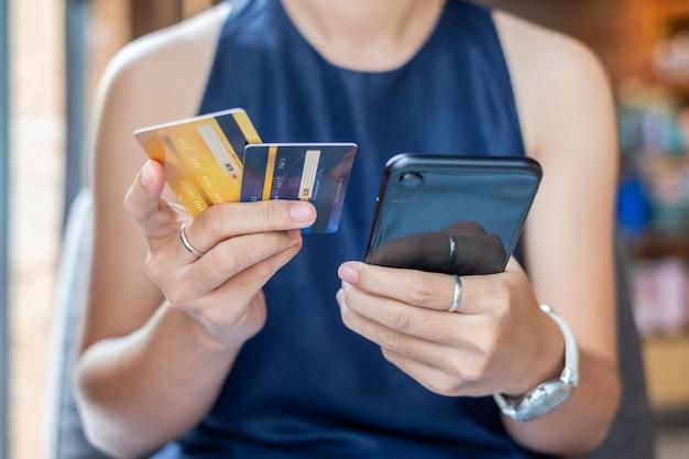 Бизнес женщина, держащая кредитной карты и с помощью смартфона