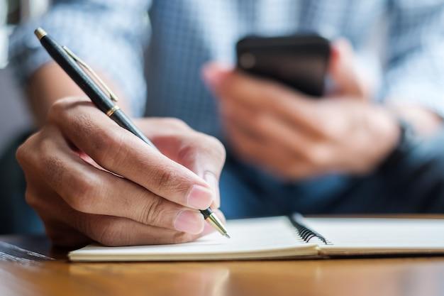 男はノートに何かを書くとスマートフォンを使用して