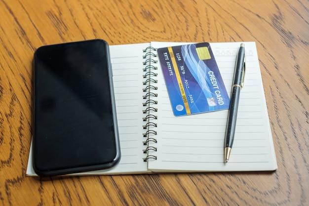 ノートブック、クレジットカード、タッチスクリーンのスマートフォンのテーブル