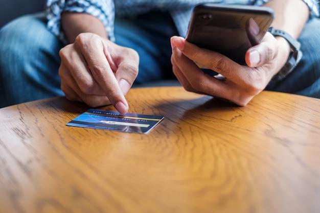 Деловой человек, держа кредитной карты и с помощью смартфона