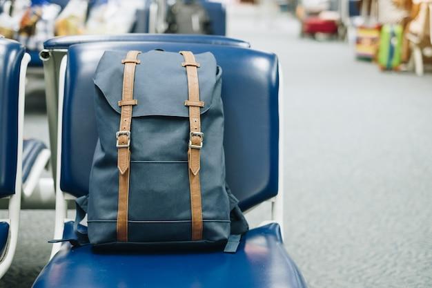 空港ターミナルのインテリアの座席に青いビンテージバッグ。旅行と学校のコンセプトに戻る
