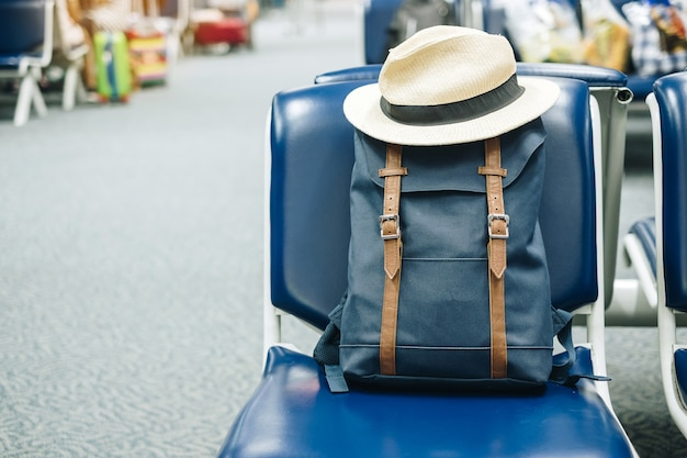空港ターミナルの内部の座席に帽子をかぶった青いビンテージバッグまたはヒップスターバックパック。旅行のコンセプト
