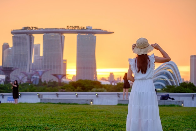 Молодая женщина путешествуя с шляпой на заходе солнца, счастливым азиатским визитом путешественника в центре города сингапура. ориентир и популярный для туристических достопримечательностей. азия трэвел концепция