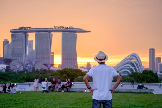 Молодой человек путешествуя с шляпой на заходе солнца, сольным азиатским посещением путешественника в центре города сингапура. ориентир и популярный для туристических достопримечательностей. азия трэвел концепция