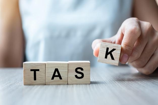 Рука коммерсантки держа деревянный блок куба с словом дела задачи на предпосылке таблицы.