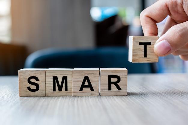 Рука бизнесмена держа деревянный блок куба с умным словом дела на предпосылке таблицы.