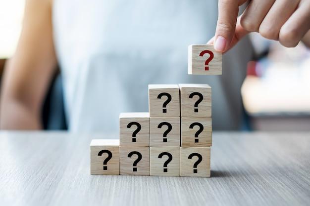 Рука предпринимателя ставит вопрос марк (?) слово с деревянным кубом