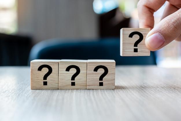 木製キューブと質問マーク(?)の単語を持っているビジネスマン手