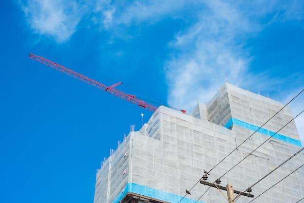 青い空にクレーンで高層ビル建設現場