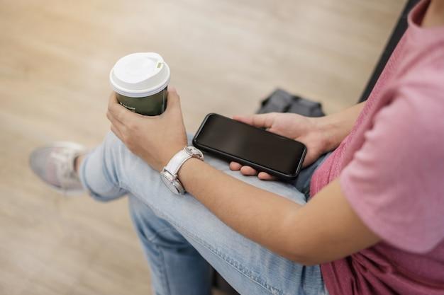 ホットコーヒーを飲む間にスマートフォンを使用します。