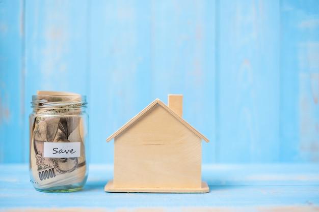 木の家のモデルとお金のガラス瓶