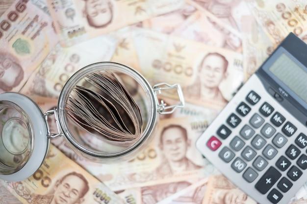 電卓とお金のガラス瓶。ビジネス、投資、退職計画、財務