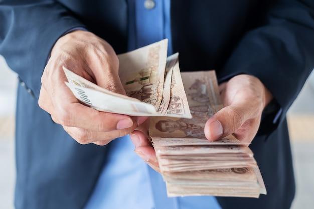 タイのバーツ紙幣スタックを持っているビジネスマン手。