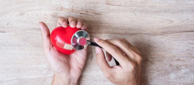 木製の背景に赤いハート形の聴診器を持つ女性の手。