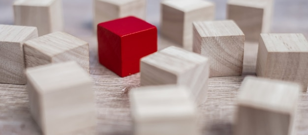 ウッドブロックの群衆とは異なる赤いキューブブロック。
