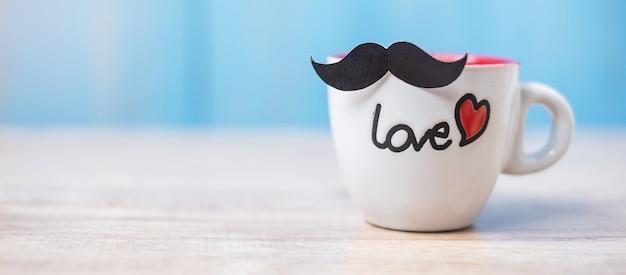 木製のテーブルに黒い口ひげとコーヒーカップ。父、国際男性デー、前立腺がん啓発