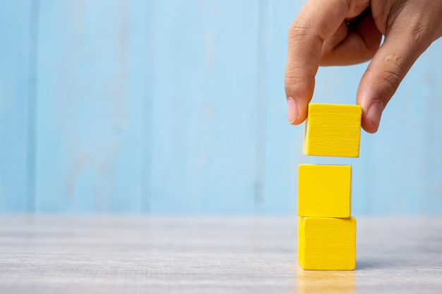 Рука бизнесмена устанавливая или вытягивая деревянный блок на здании. бизнес-планирование, управление рисками, решения, стратегии, разные и уникальные