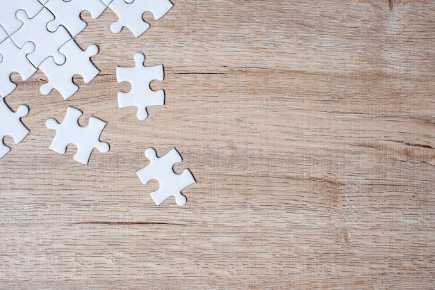 Кусочки головоломки на фоне дерева стол