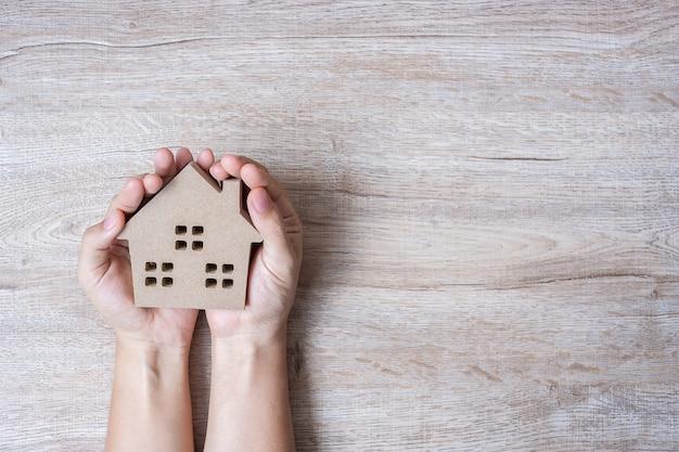 コピースペースを持つ木製テーブル背景に家モデルを保持している手。