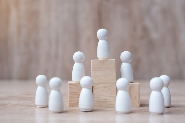 Вручите держать верхнюю часть руководителя бизнесмена с толпой деревянных людей.