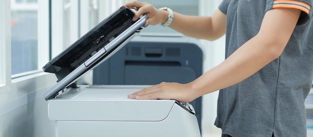 Ручная установка бумажной бумаги в лазерный копировальный аппарат для сканера принтера в офисе