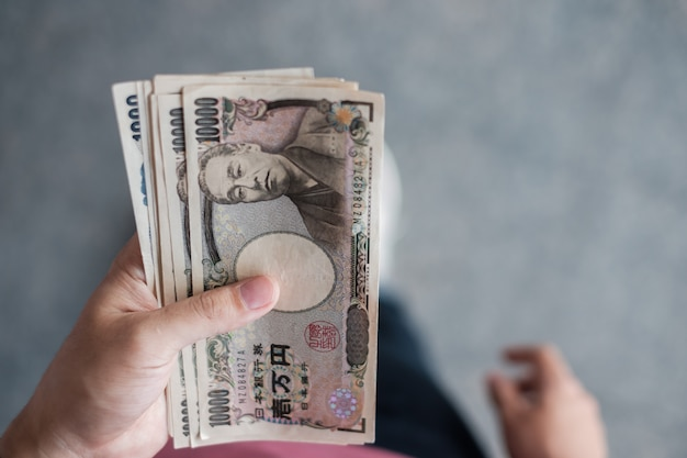 Рука коммерсантки держа стог банкноты японских иен. концепции бизнеса, денег, инвестиций, финансов и платежей