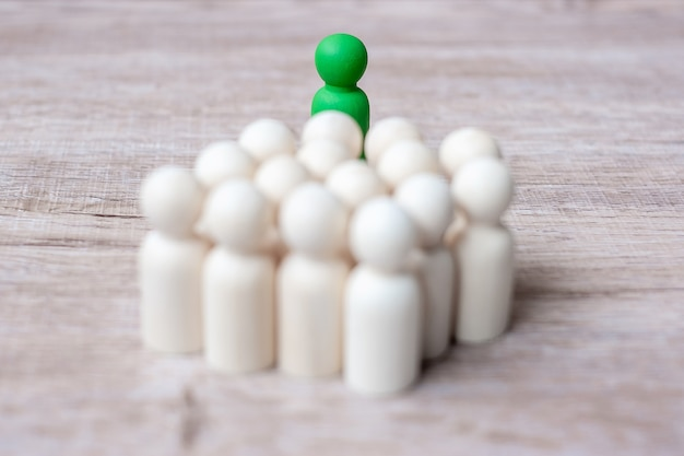木製の男性の群衆の中に緑のリーダー実業家。リーダーシップ、ビジネス、チーム、チームワーク、人的資源管理の概念