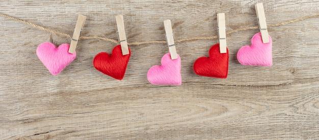 テキストのコピースペースが付いているラインに掛かっている赤とピンクのハート形の装飾。愛、結婚式、ロマンチックで幸せなバレンタインの日の休日の概念