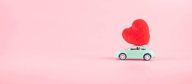 ピンクのテキストのコピースペースを持つミニ車のおもちゃに赤いハート形の装飾。愛、結婚式、ロマンチックで幸せなバレンタインの日の休日の概念