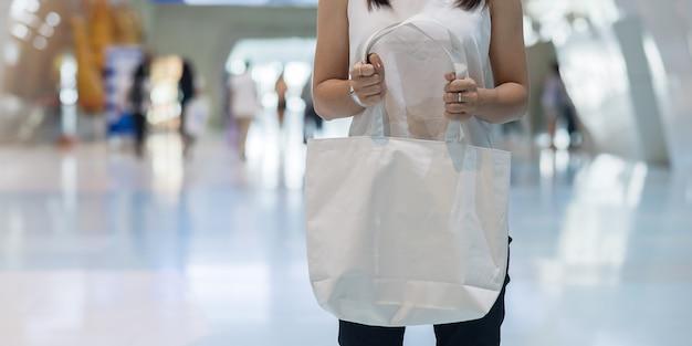 テキストのコピースペースを持つストアでエコショッピングバッグを持つ女性の手。環境保護、廃棄物ゼロ、再利用可能、プラスチックとは言わない、世界環境の日、地球の日の概念
