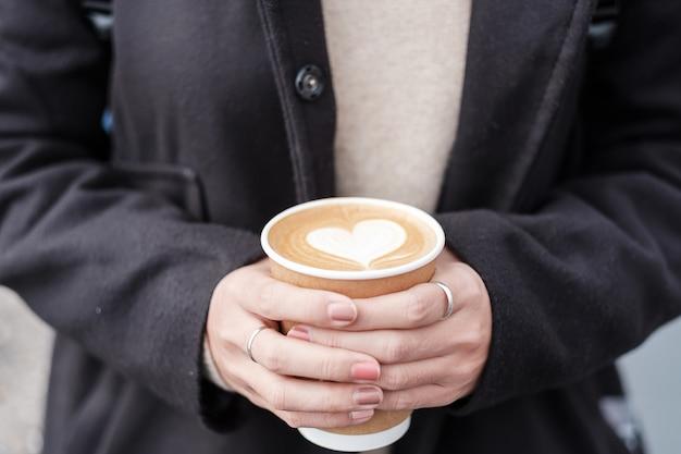 ホットコーヒー紙コップ、ハート形のラテコーヒーアートを保持している女性の手。愛、休日、バレンタインデー、無料のプラスチック容器のコンセプト