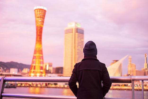 大阪近くの神戸港、夕暮れ時の美しいモダンな建物を探して幸せなアジア旅行者で旅行する若い女性。兵庫県神戸市の観光スポットで人気のランドマークとアジア旅行コンセプト