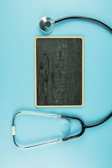 テキストのコピースペースと青色の背景に平面図聴診器。ヘルスケア、生命保険、健康の日、世界心臓デー、幸せな医者の日の概念