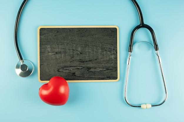 テキストのコピースペースと青い背景に赤いハート形の平面図聴診器。ヘルスケア、生命保険、健康の日、世界心臓デー、幸せな医者の日の概念