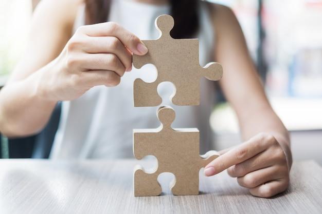 テーブルの上のカップルのパズルを接続する女性の手、オフィス内の木製ジグソーパズルを保持している実業家。ビジネスソリューション、使命、目標、成功、目標、戦略の概念