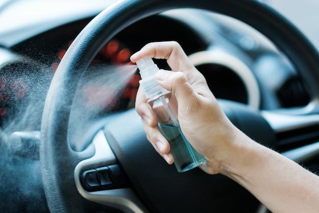 男の手が彼の車のステアリングホイールにアルコール消毒剤を噴霧します。防腐剤、衛生およびヘルスケアの概念
