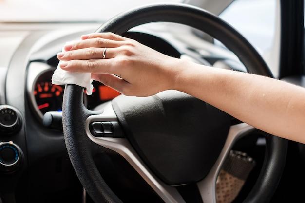 女性の手が彼の車のステアリングホイールのクリーニング。防腐剤、衛生、ヘルスケアのコンセプト